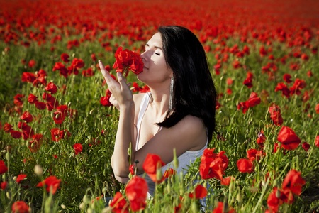 young woman on the beautiful poppy field photo