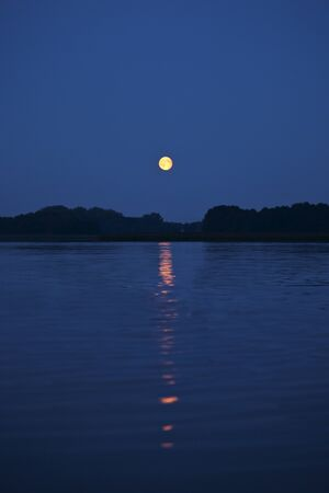 shining moon and its reflection in the Wigry lake photo