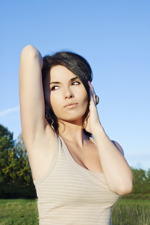 armpits: a pretty woman posing on the sky background Stock Photo