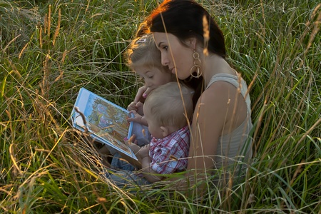 mum reading book for her two children photo
