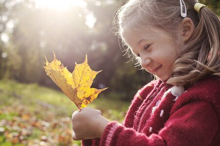 a little smiling girl with a yellow autumn leaf Stock Photo - 11481610