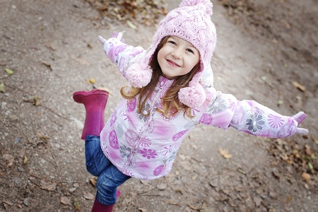 happy smiling girl in a wooly pink hat and winter jacket