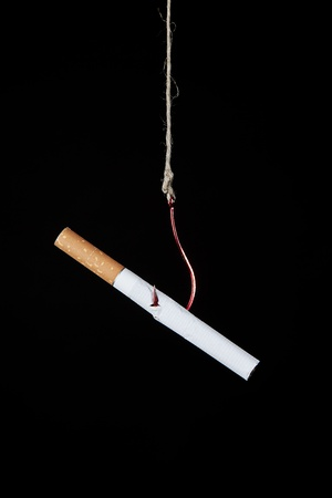nicotine: a cigarette hanging on a hook as a symbole of nicotine addiction Stock Photo