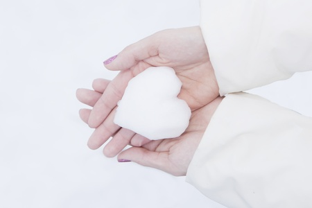 formed: woman hands holding heart formed from snow