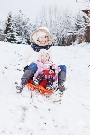 sledding: mum and daughter having a sledge ride on snow