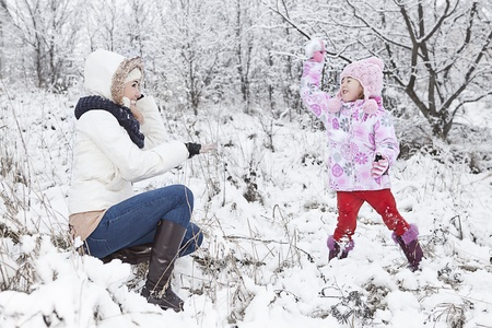 family fight: mum and daughter havin fun on the snow Stock Photo