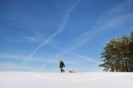 tata ciągnie swoją córkę siedzi na saniach na śniegu