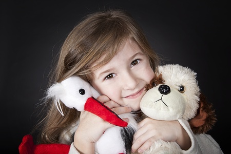 smiling girl hugging toy stork and dog Stock Photo - 12770828