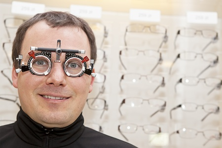 hyperopia: smiling man with eye check glasses on Stock Photo