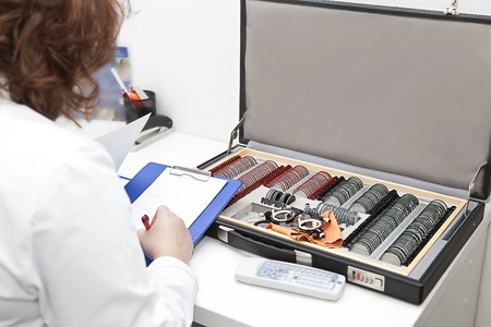 a woman optometrist and the suitcase with sight testing set photo