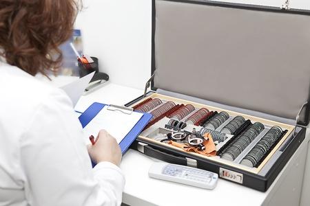 optometrist kobieta i walizka z zestawem testów wzroku