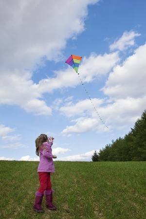 little girl with colofrul kite on sky background