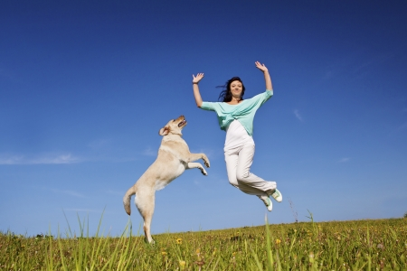 happy beautiful girl jumping up together with her dog Stock Photo