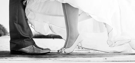 legs of bride and groom standing on a bridge