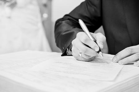 firmando: mano de un hombre de negocios que firma un documento muy importante