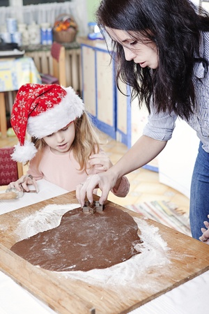 mum and her daughter cutting gingerbread cookies photo