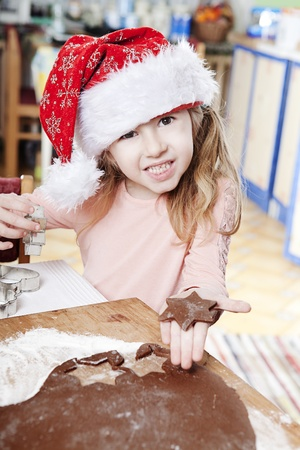 little girl in santas hat doing star shaped gingerbread cookies photo