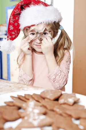 little girl playing while preparing christmas sweets photo