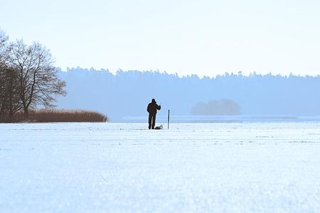 Ice Fishing in winter scene photo