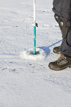 ice fishing: Ice auger -  tool is for drilling  fishing hole in the ice