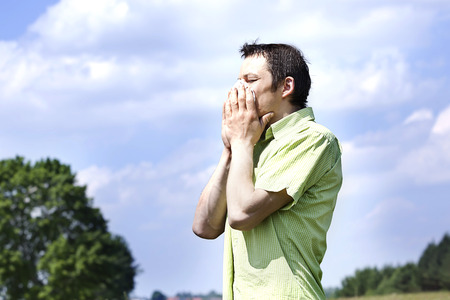 sniffles: man sneezing because of pollen allergy in a garden in the spring