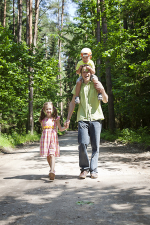 Dad , son and daughter   on a walk in the woods photo