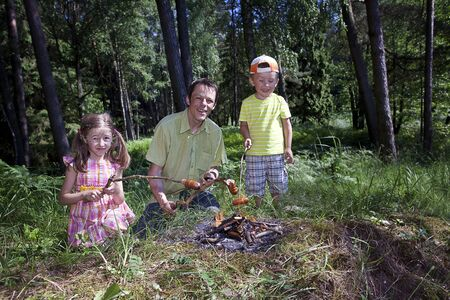 Parent with daughter and son near campfire frying sausages photo