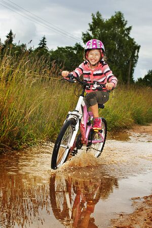 A small, happy girl goes by bicycle on a dirt road after a puddle photo