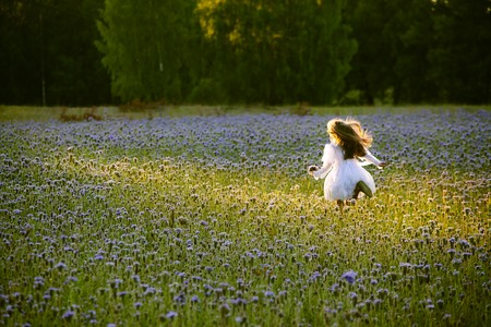 happy little  girl in a white dress running on meadow flowers at sunset