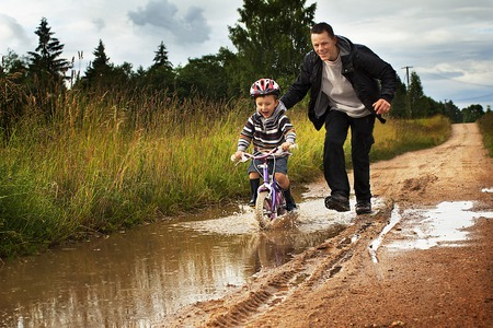 Dad teaches a little boy ride a bike around puddles to exercise better coordination and a steering photo
