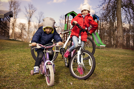 Girl and boy cycling in autumn time photo