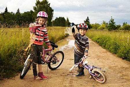 out of water: kids pour out water from shoes after playing on the bikes   in the puddle