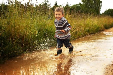 after the rain happy boy runs through a puddle Standard-Bild