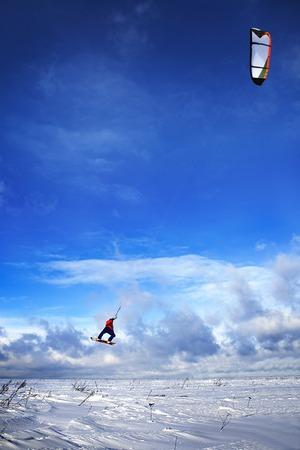 snowkiting: Winter landscape with snowkiting man jumps on board Stock Photo