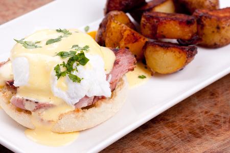 papas doradas: huevos Benedict con huevos y jamón frescos de granja y las patatas fritas Foto de archivo