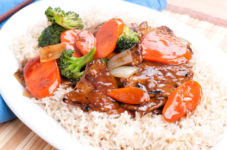 beef with broccoli and carrot stir fry over brown rice Stock Photo
