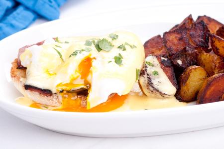 papas doradas: huevos Benedict con huevos y jam�n frescos de granja y las patatas fritas Foto de archivo