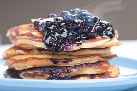 flapjacks: a stack of blueberry pancakes with butter, syrup and fresh berries
