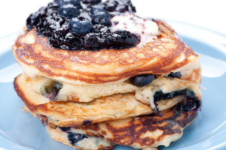 a stack of blueberry pancakes with butter, syrup and fresh berries