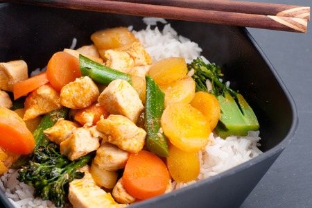 Thai coconut and mango curry with diced chicken and sliced carrots over coconut rice