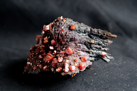 red stone: red vanadinite crystal mineral sample on metamorphic rock Stock Photo