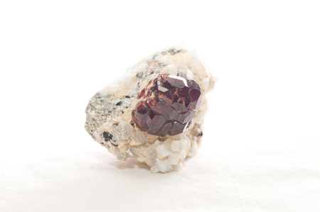 hydrothermal: a large spessartine garnet embeded in quartz and granite