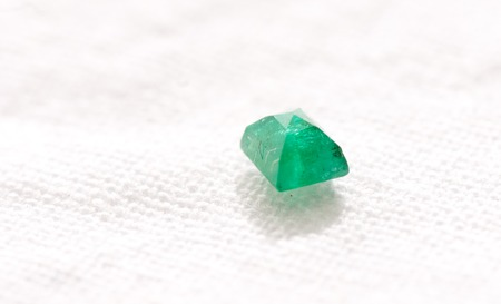 lapidary: vibrant green beryl jewel cut crystal on a white background
