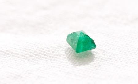 beryl: vibrant green beryl jewel cut crystal on a white background
