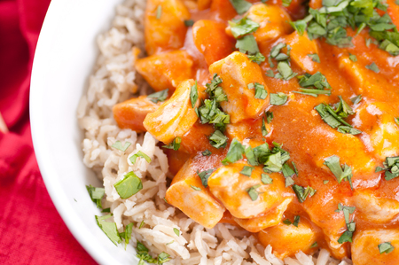 spicy butter chicken over brown rice with cilantro Stock Photo