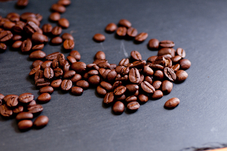 cafe colombiano: coffee beans from south america dark roasted on an artistic slate background Foto de archivo