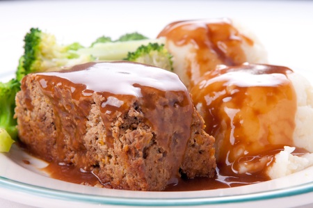 pure de papa: delicious meatloaf with mashed potatoes, gravy and fresh vegetables Foto de archivo