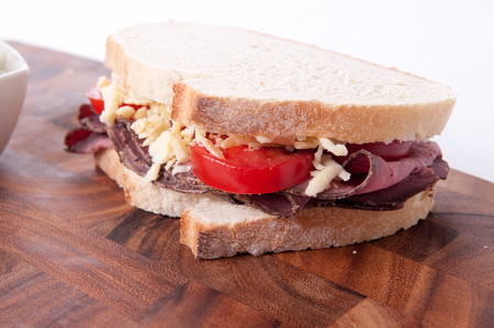 french roll: sliced roast beef sandwich with cheese and tomato and cole slaw
