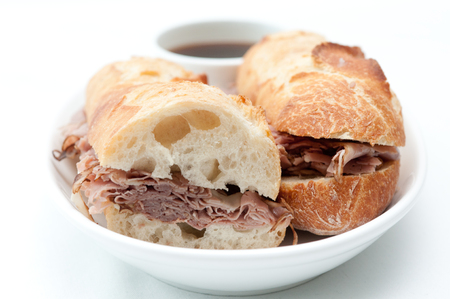 jus: a french dip or beef dip on a baguette with dipping sauce or au jus