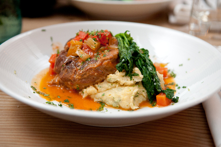 osso buco made with polenta and a tomato sauce with fresh greens